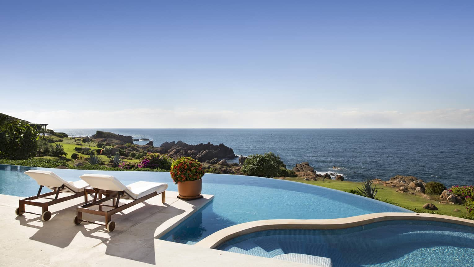 Terrace with two lounge chairs and large infinity pool, overlooking the sea