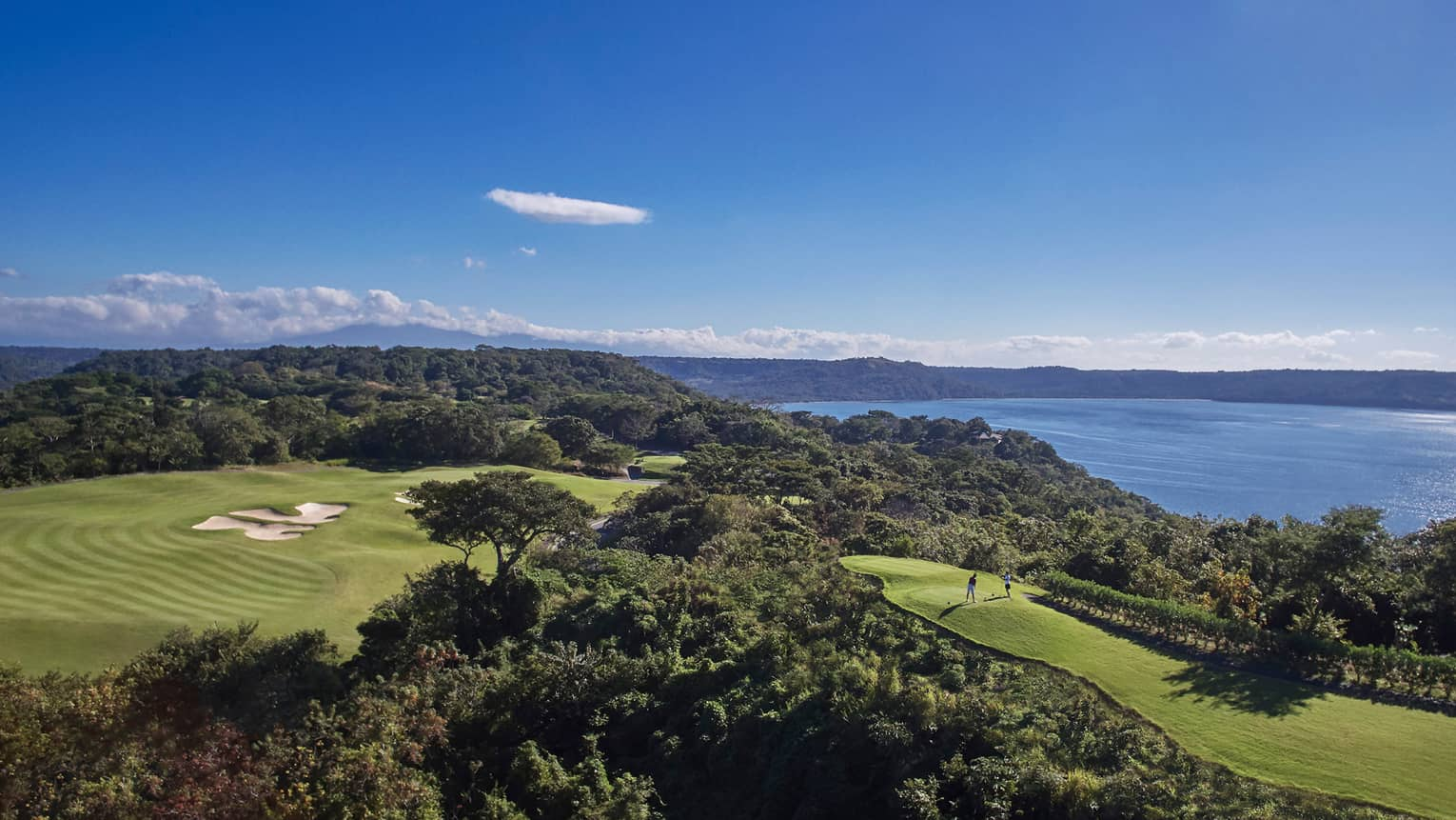 Looking down at large golf course green, trees on top of mountain, two players on hole, ocean view