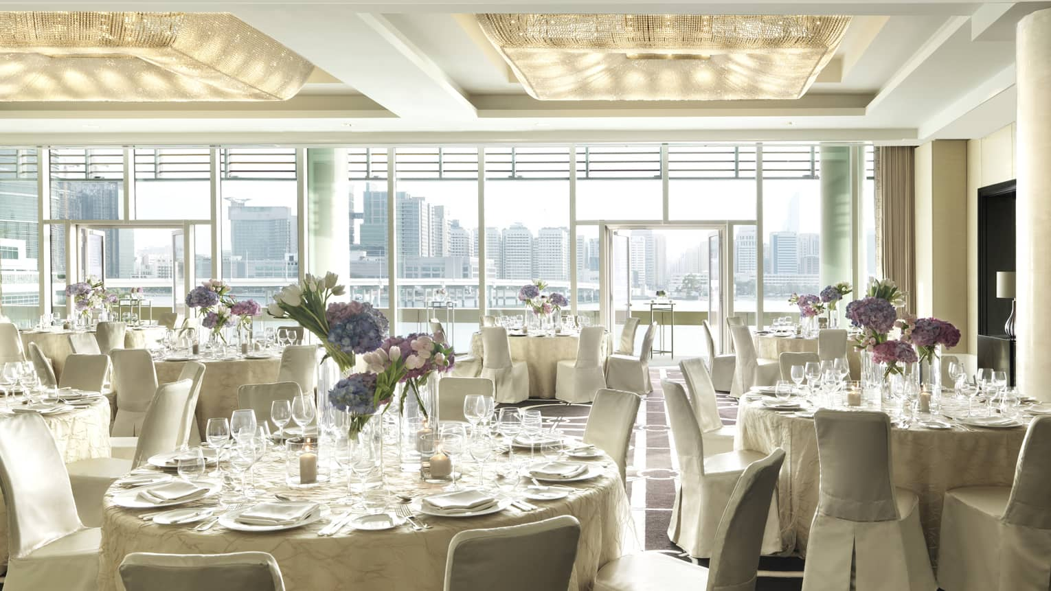Sunny Liwa Ballroom with floor-to-ceiling window, round banquet tables with white linens, chairs