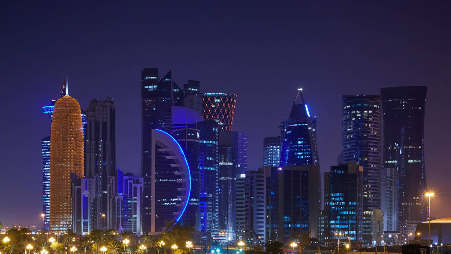 Doha skyline at night with blue lights, lit skyscraper windows