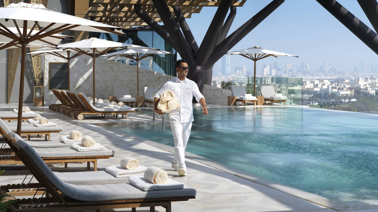 Hotel staff walks past white lounge chairs on outdoor swimming pool deck, carries rolled towels