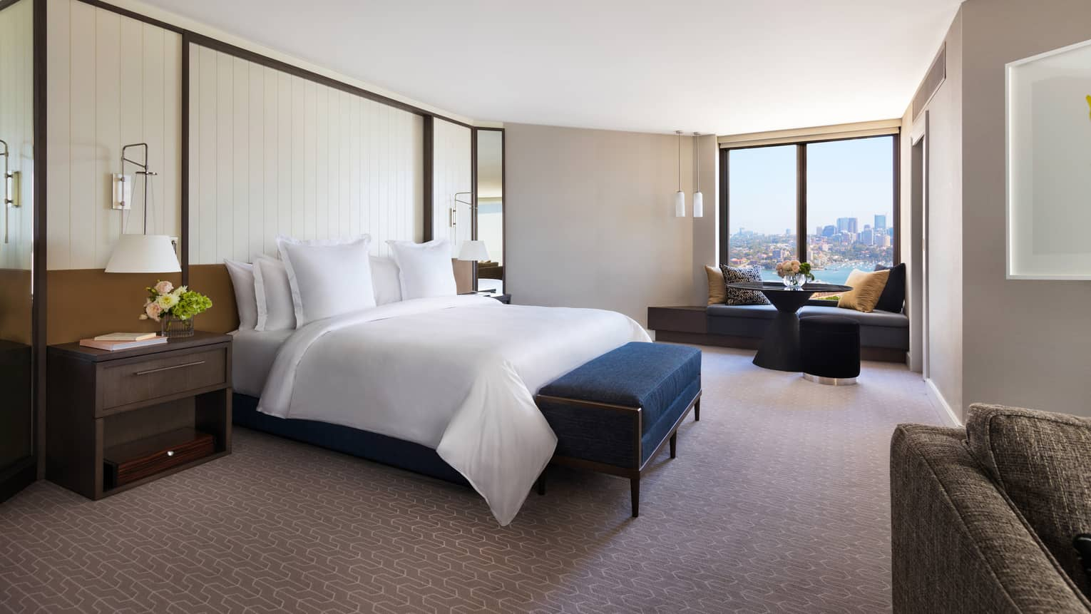 Spacious hotel room with king bed and partial views of Sydney Harbour