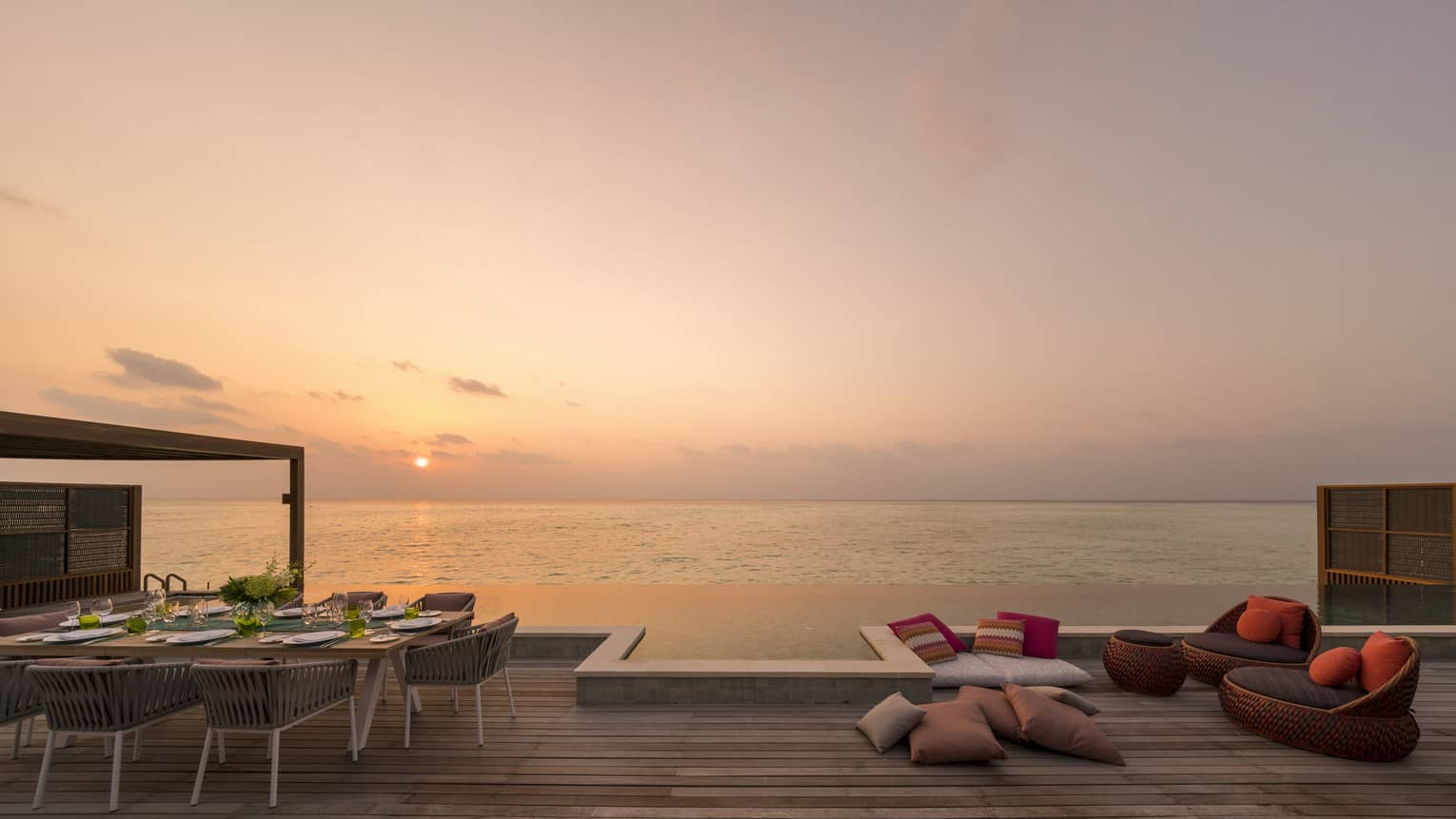 Large wooden deck with dining table and lounge chairs, overlooking an ocean sunset