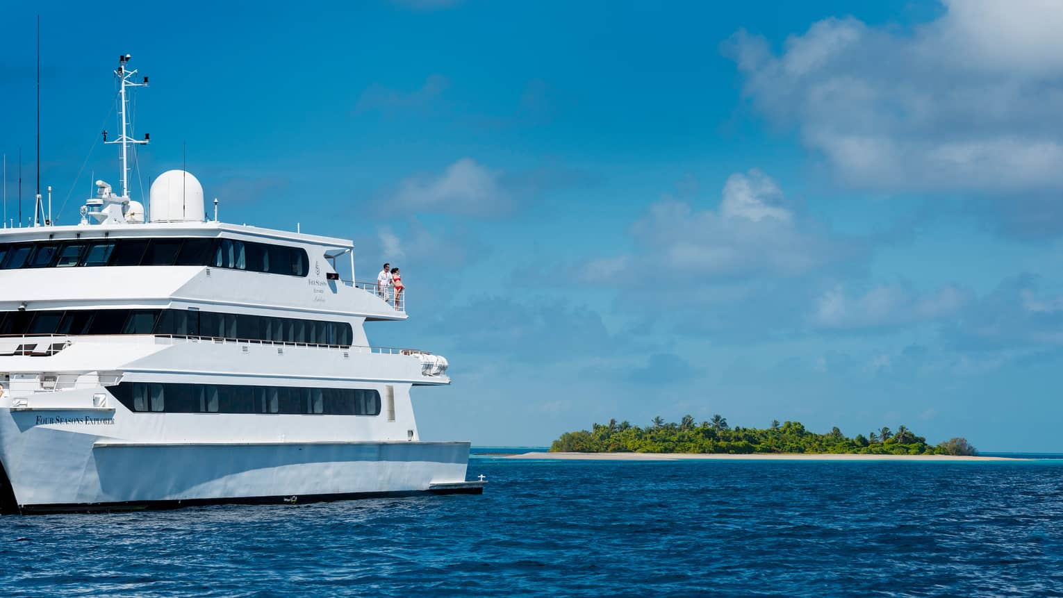 Couple on third-storey balcony of white catamaran yacht on ocean near small private atoll