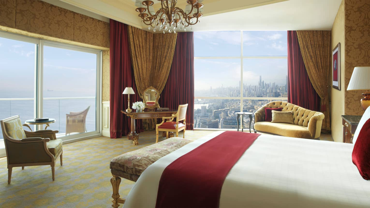 Royal Suite hotel room with red velvet pillow and blanket, chandelier with crystals, red-and-gold accent chairs