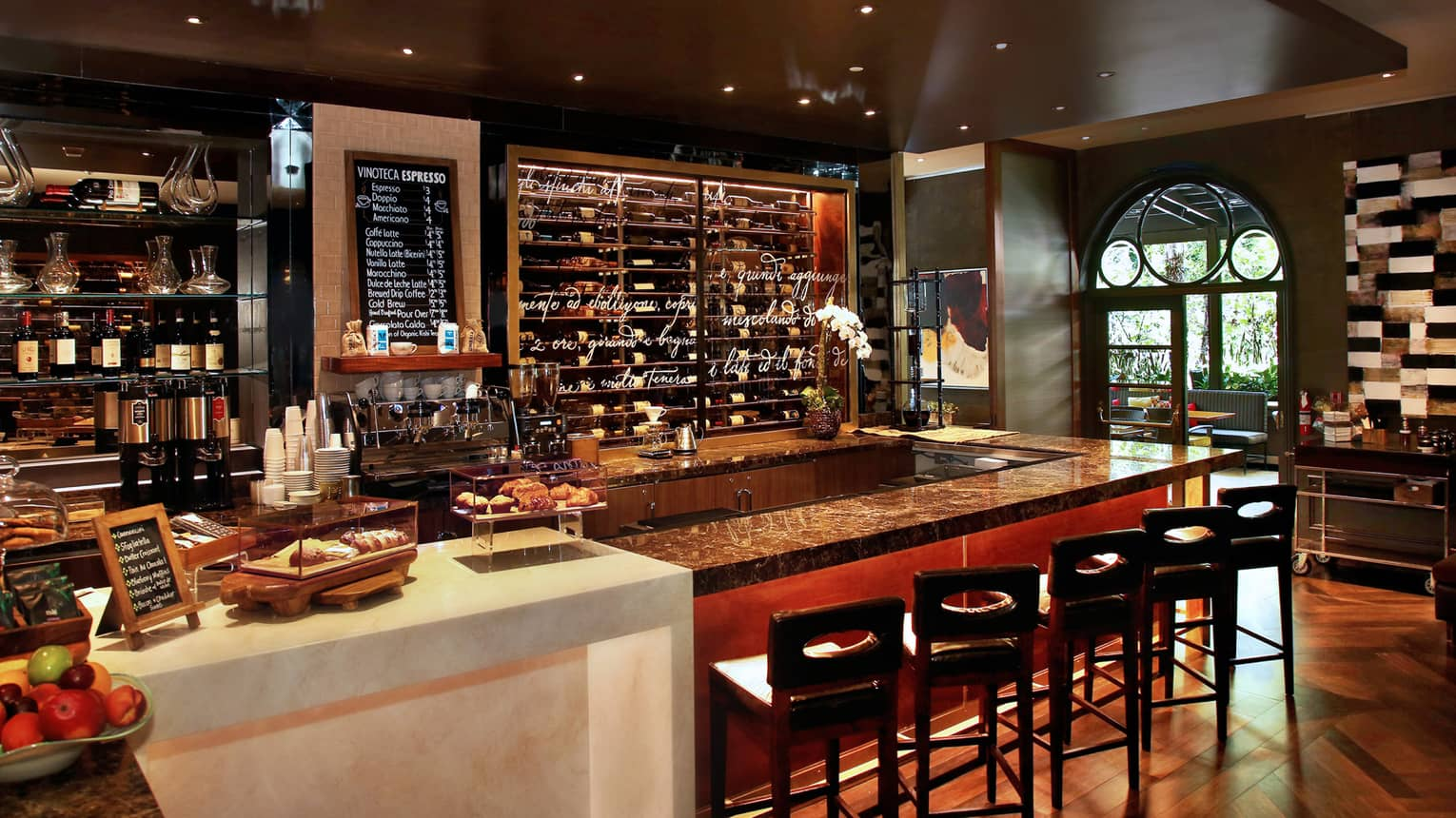 Vinoteca lounge bar lined with stools in front of glass wall, wine rack, chalk board with espresso options