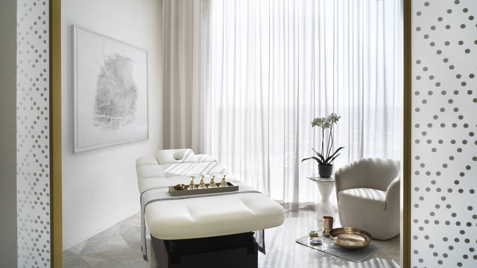 Spa room with a white massage table and white chair, next to a large window covered by a sheer curtain