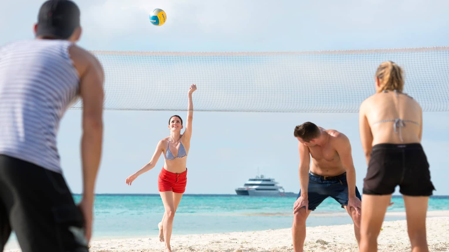 Woman serves volleyball over net as group of friends play on white sand beach