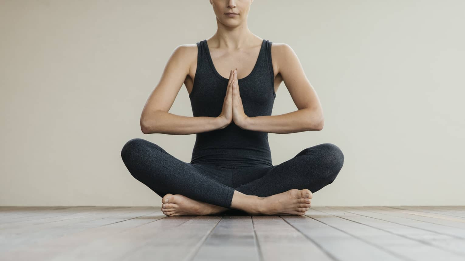 Woman wearing black sits cross-legged on floor in yoga prayer pose