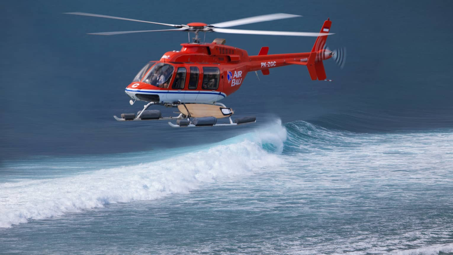 A helicopter hovers over the water for a guest to go helisurfing