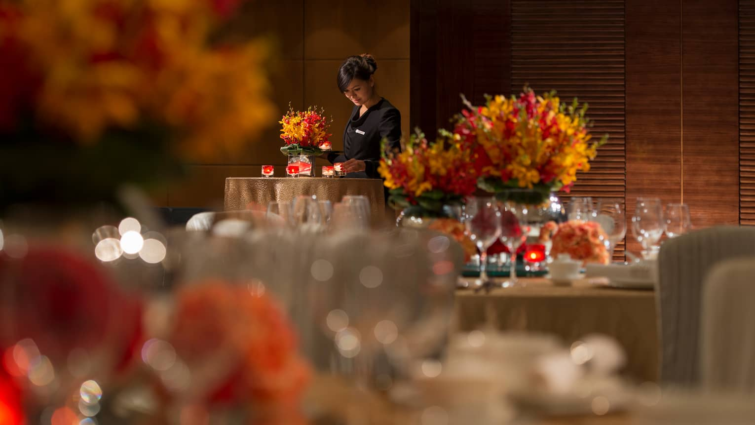 Hotel server in uniform places candles on table with orange flowers, linens, behind dining tables
