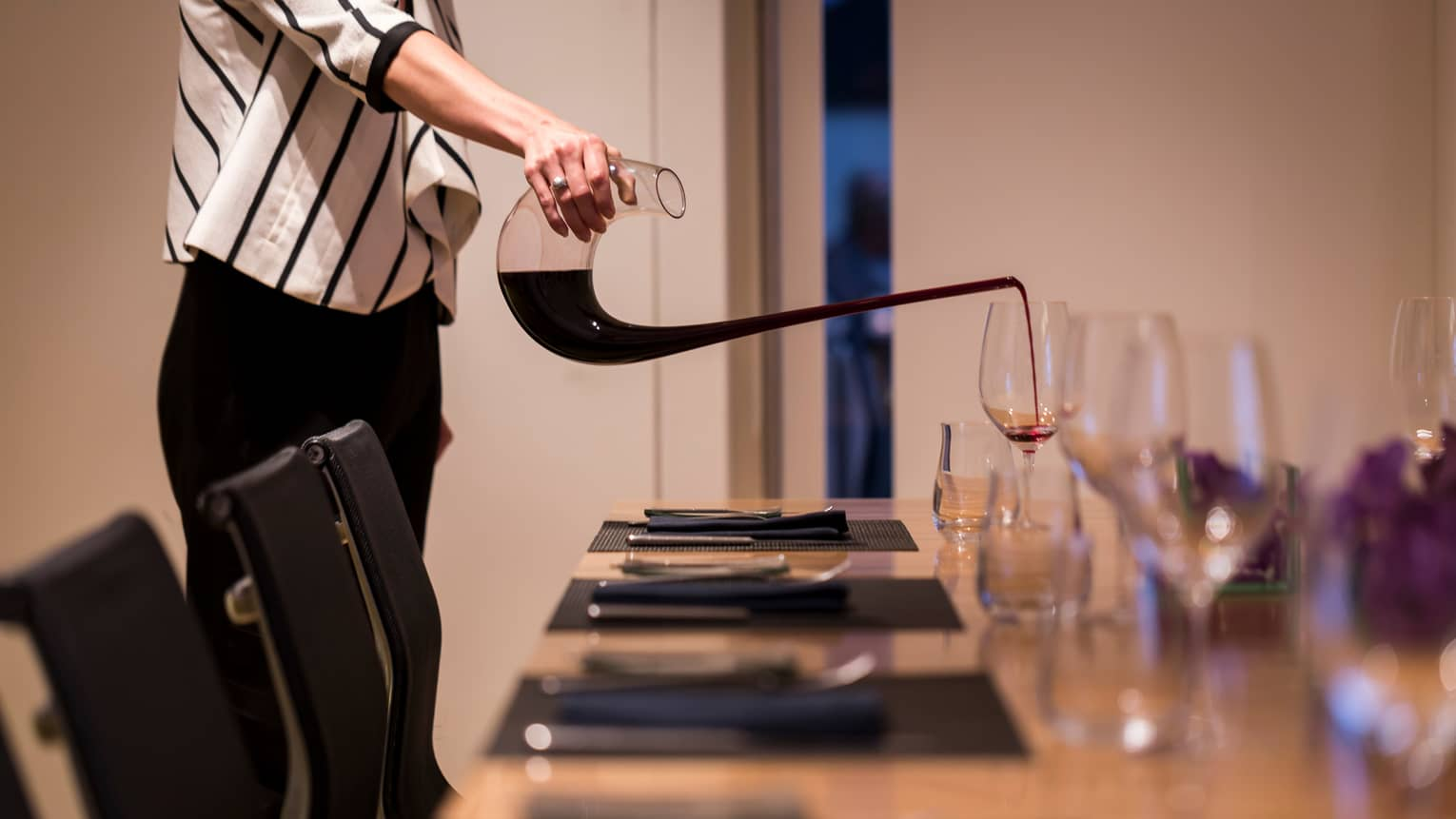 Close-up of woman in striped jacket pouring red wine into glass on meeting table