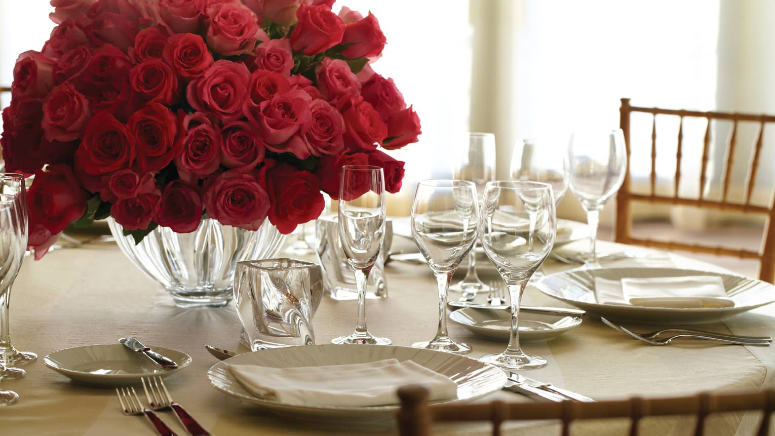 Banquet dining table place setting with plate, crystal glasses and vase with red rose bouquet