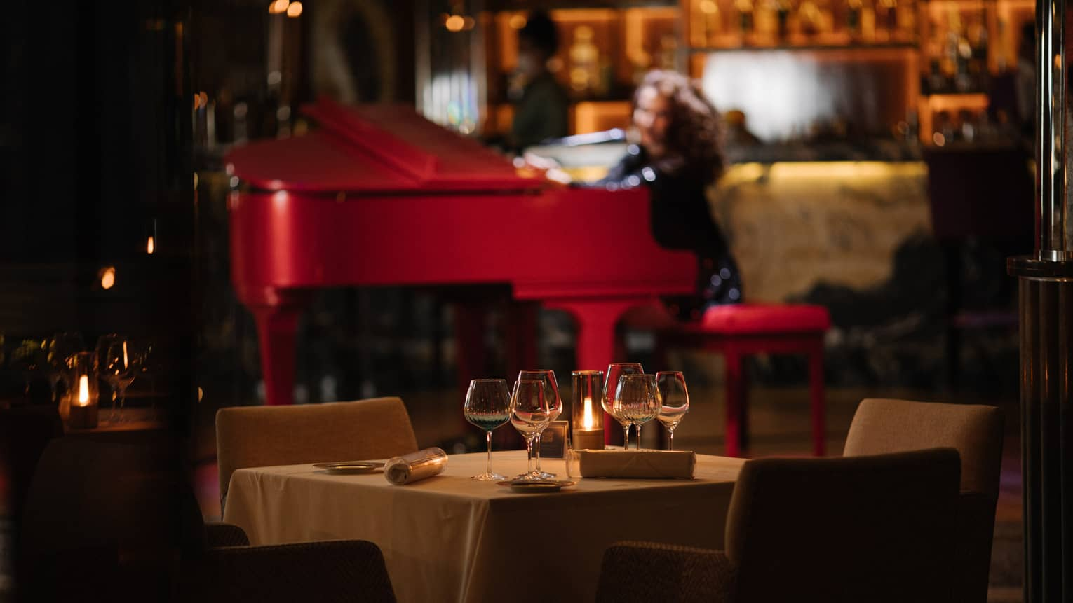 Pianist at red baby grand in backdrop of dimly lit restaurant lounge