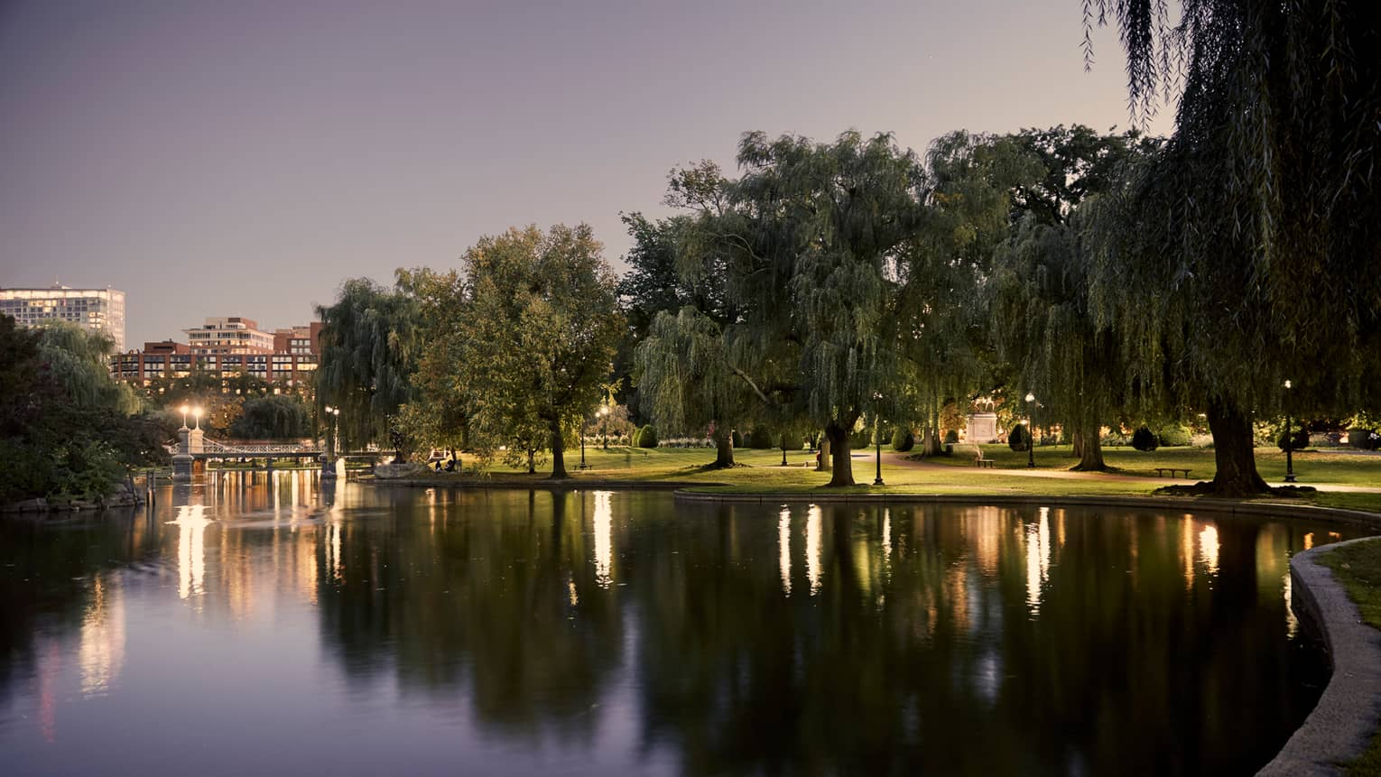 Boston Public Garden pond lined with large trees, lights at dusk