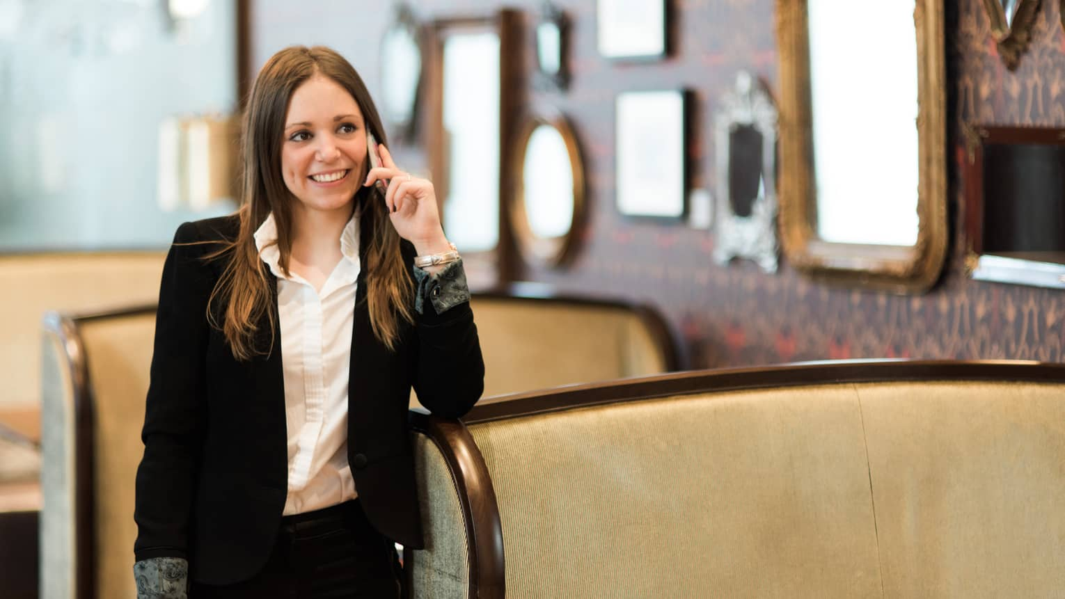 Woman in suit smiling and holding phone standing next to banquette with mirrors on wall