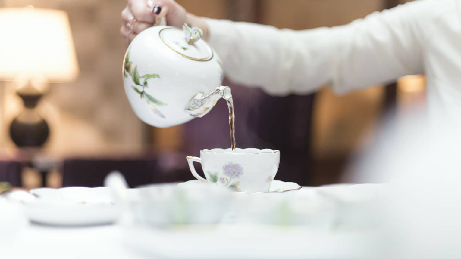 Person holds floral tea pot and pours tea into cup and saucer
