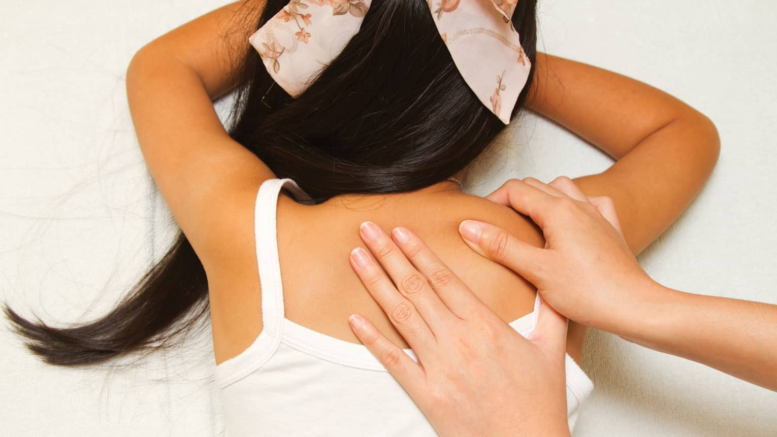 Masseuse hands massage girl's shoulders