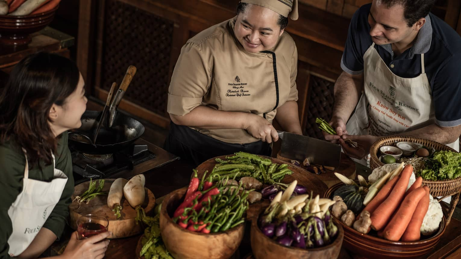 Chef chops mushrooms in front of couple, bamboo baskets with vegetables
