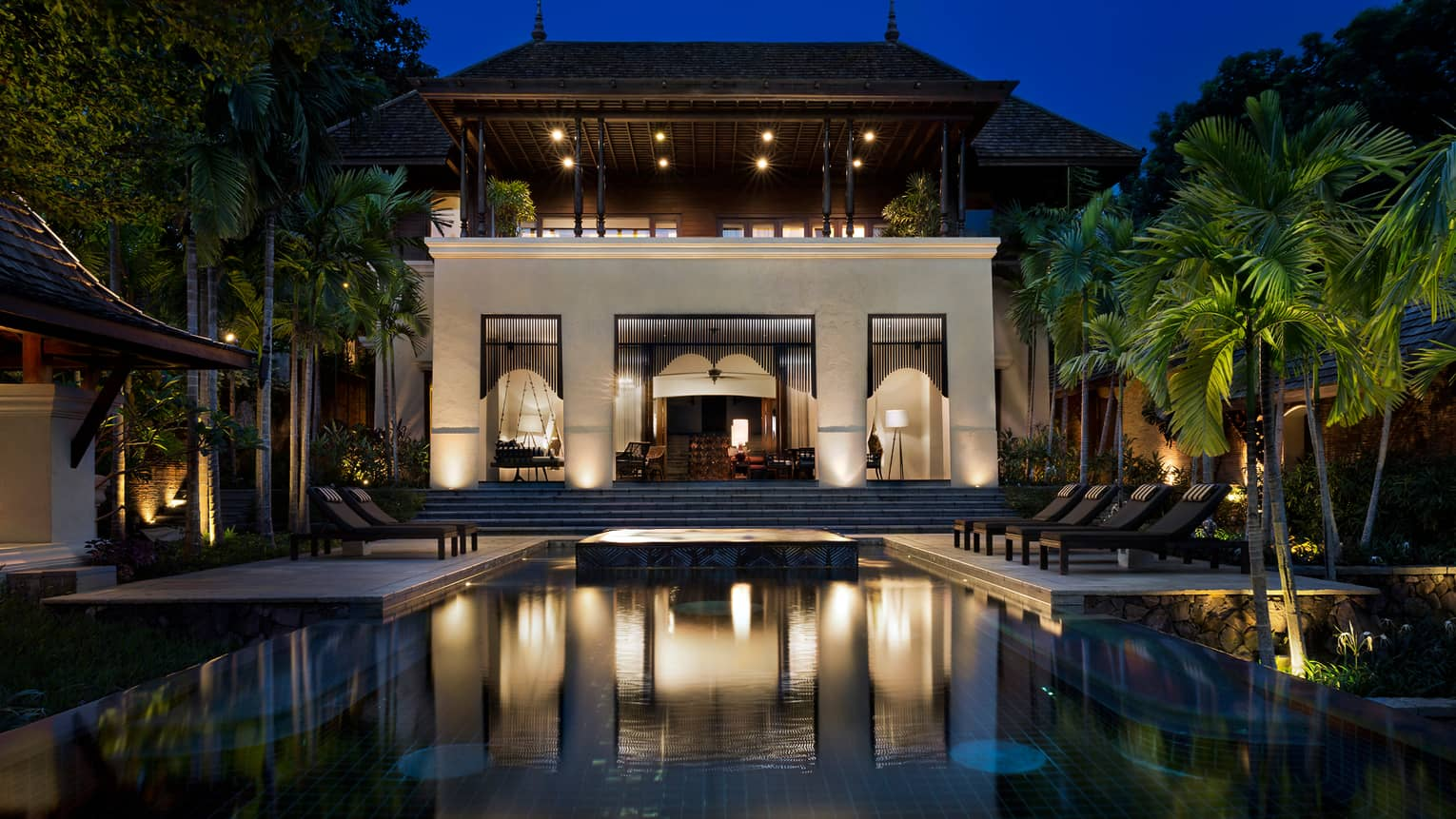 Large Four-Bedroom Residence Villa at night with lights, outdoor pool and palms