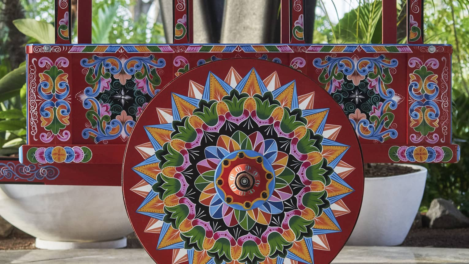 An intricately painted cart has floral designs in a rainbow of colors