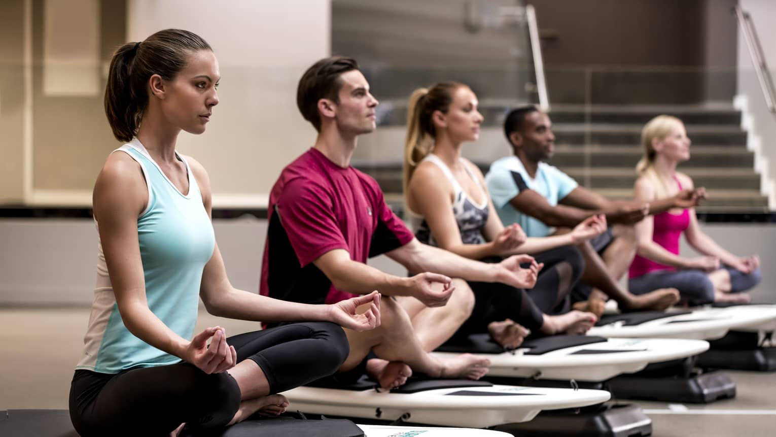 Row of people sitting cross-legged in meditation poses on small boards in Fitness Centre