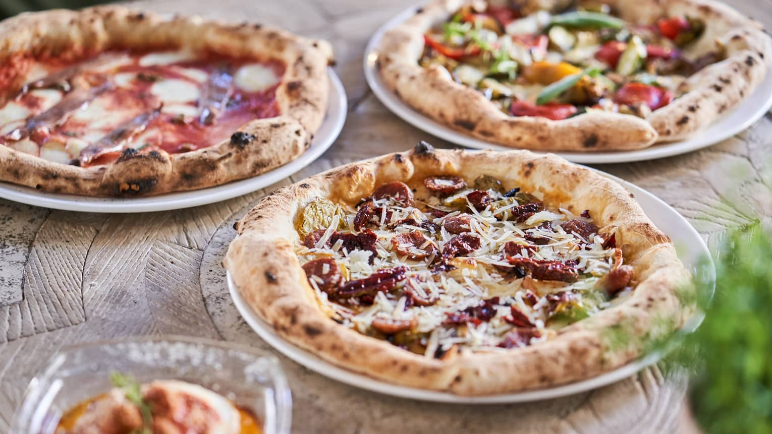 Three signature pizzas, each with unique, vibrant toppings