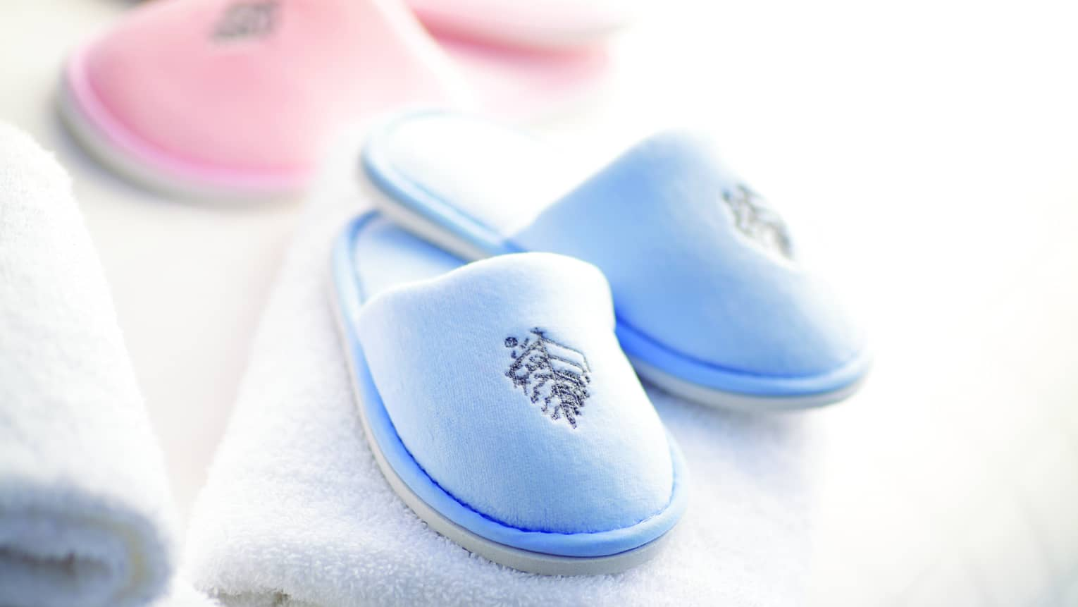 A pair of baby pink and baby blue kid's spa slippers and fluffy white towels