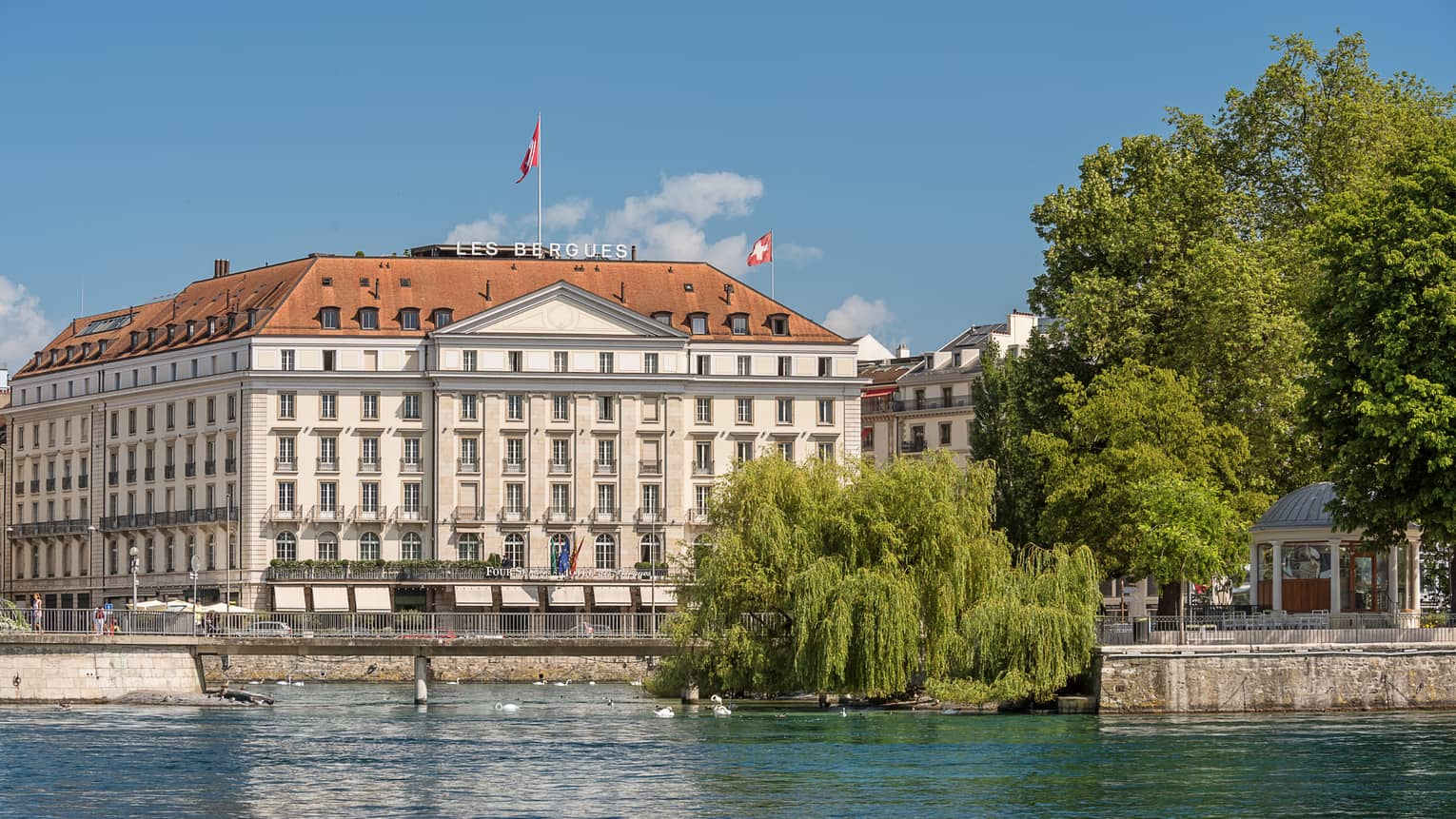 Exterior view of Four Seasons Hotel des Bergues historic building on sunny day by lake