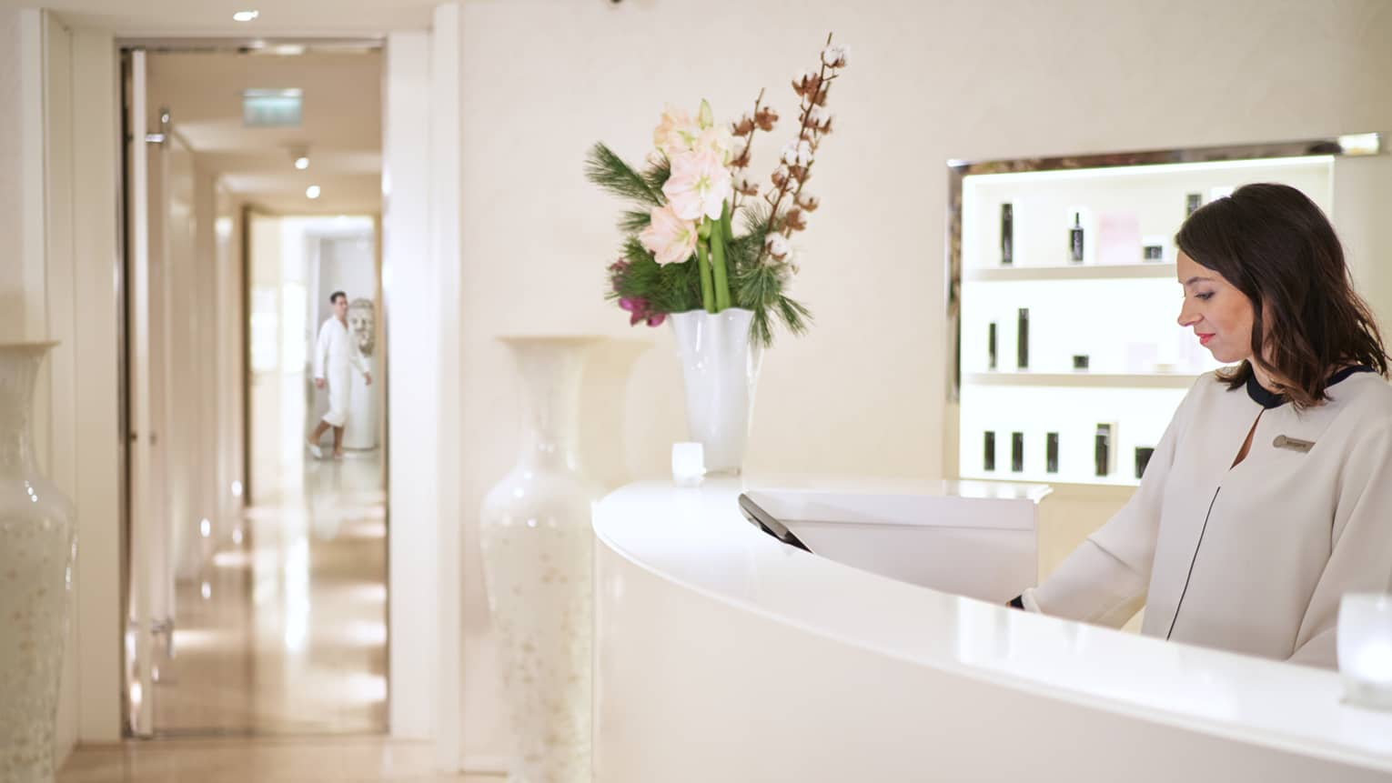 Staff member in white jacket standing behind curved white reception desk with flower vase, view into spa hallway