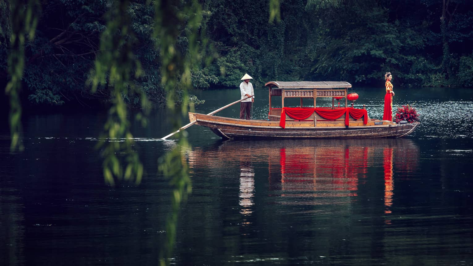 View across pond to bride wearing traditional red wedding gown at end of small boat