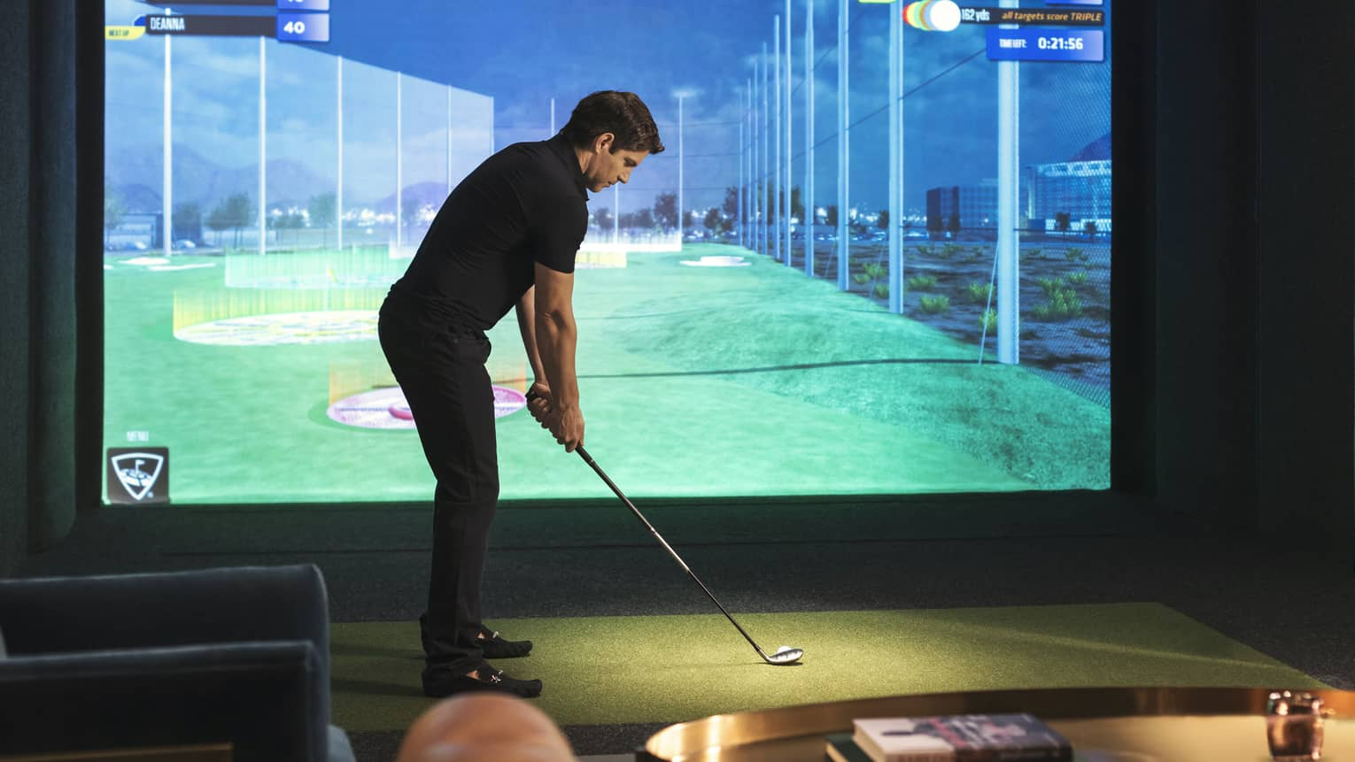 Man with golf club stands in front of screen showing Virtual Fairway