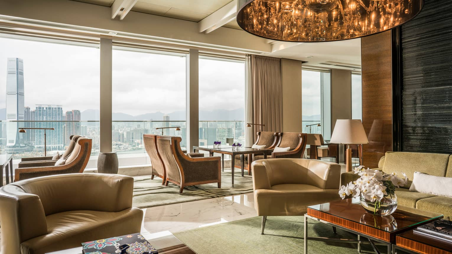 Executive Lounge seating areas with sofas, curved armchairs, bright floor-to-ceiling window, city views