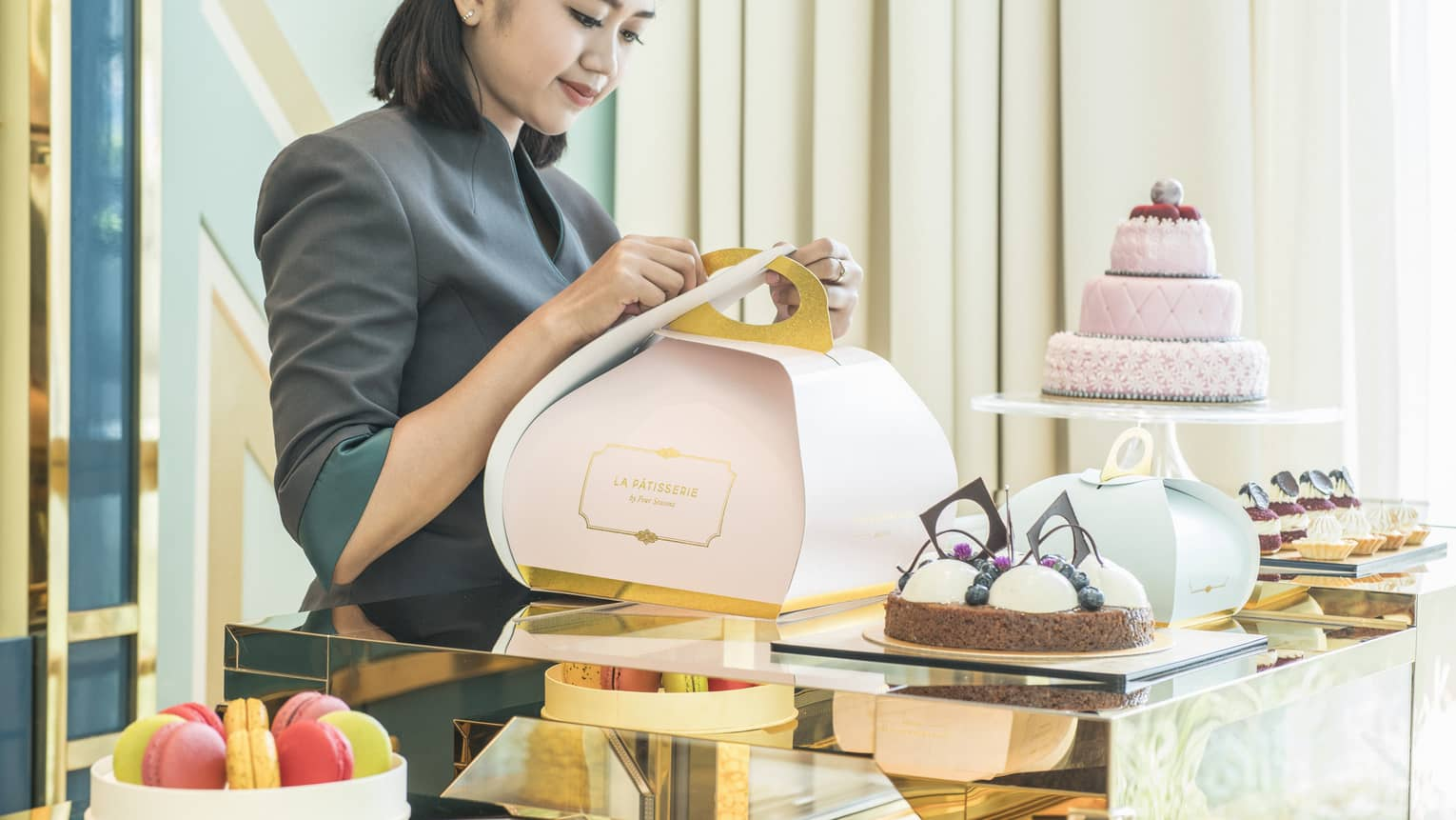 Woman wrapping a pastry in a stylish light pink box for take away