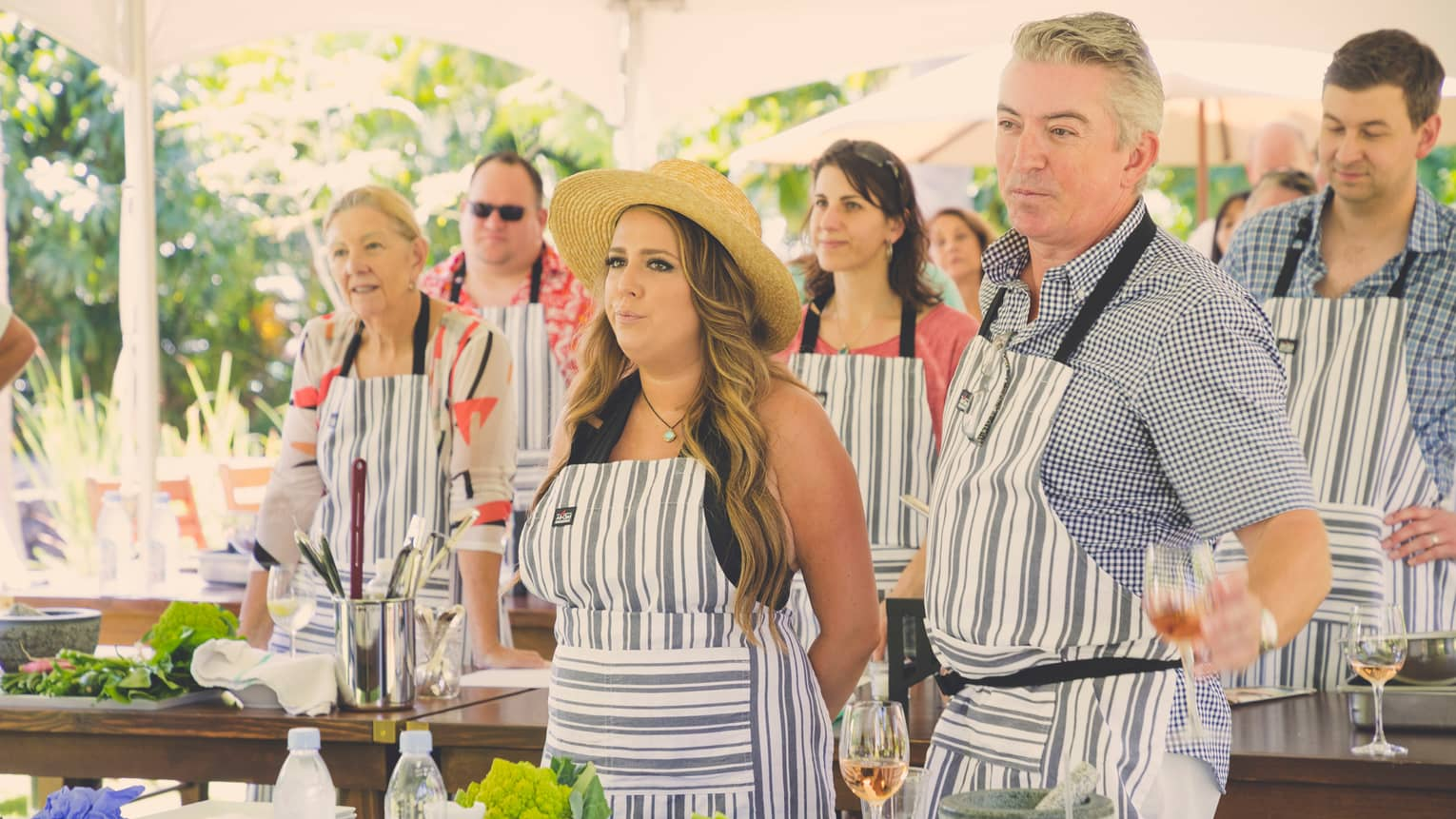 People wearing striped aprons stand at tables with fresh vegetables, cooking class