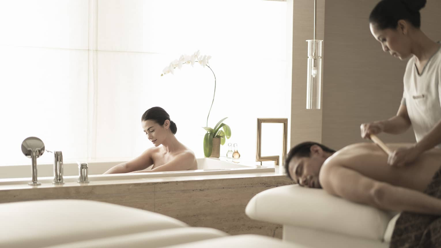 Woman soaks in spa tub near man getting massage