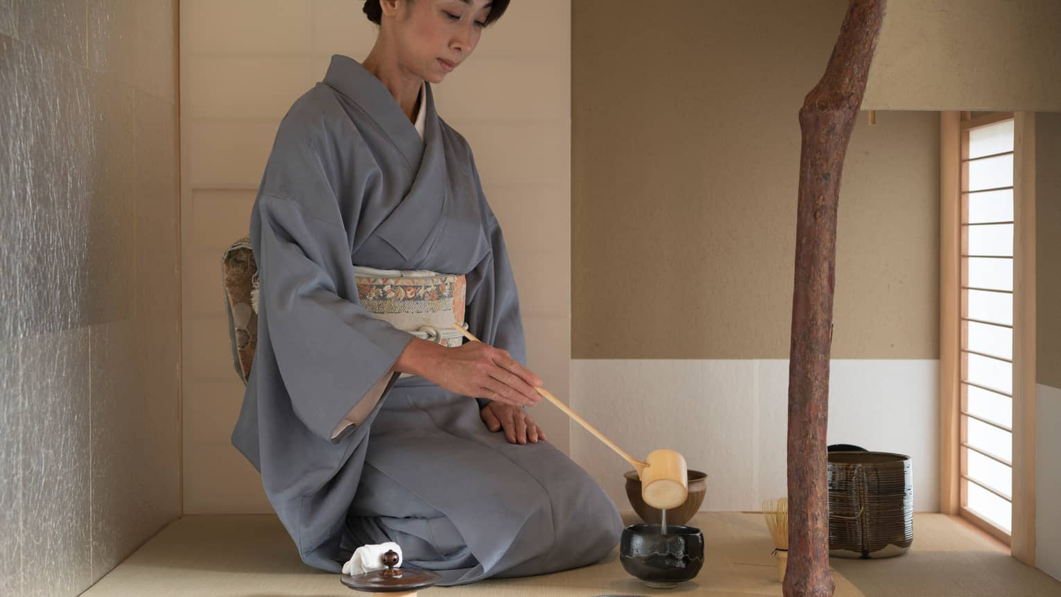 Woman in robe kneels on floor, ladles tea into cup with wood spoon