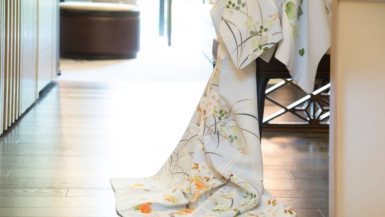 Close-up of kimono robe with floral print hanging over side of chair