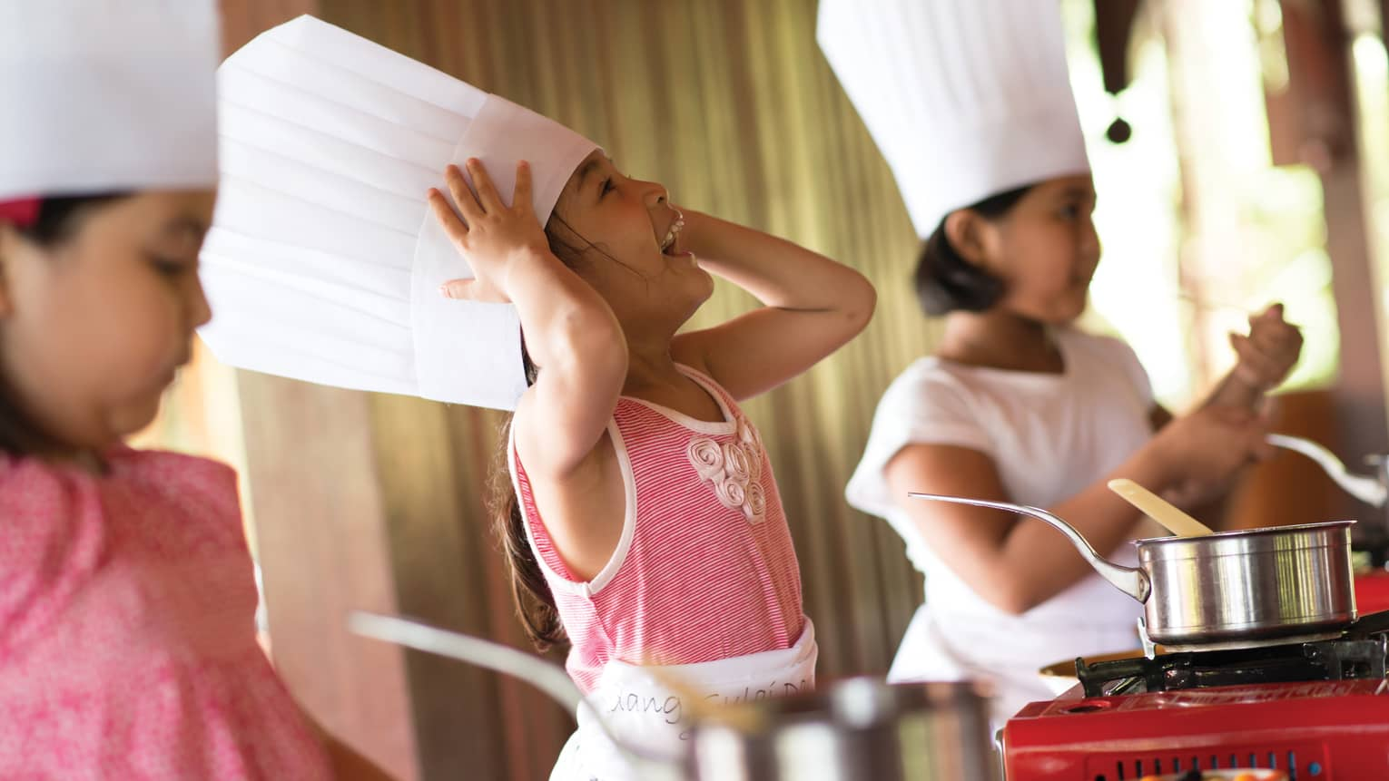Three young children wearing tall white chef's hats in cooking class