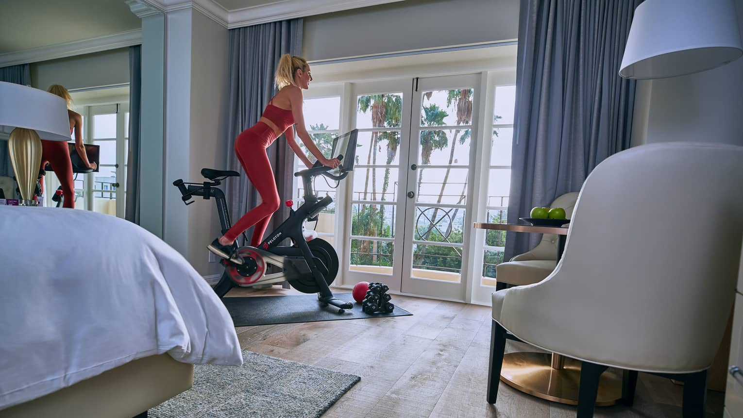 Woman wearing red exercise clothes works out on cardio bike beside sunny balcony door