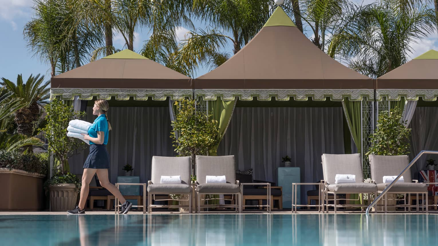 Hotel Staff Carries Stack Of White Towels Past Cabanas On Outdoor Swimming Pool Deck