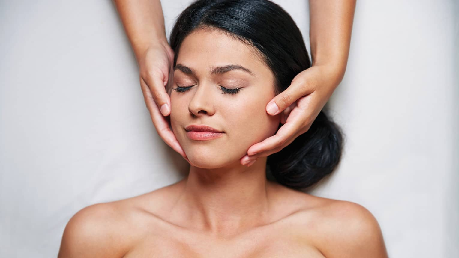 Woman with eyes closed as hands massage her face