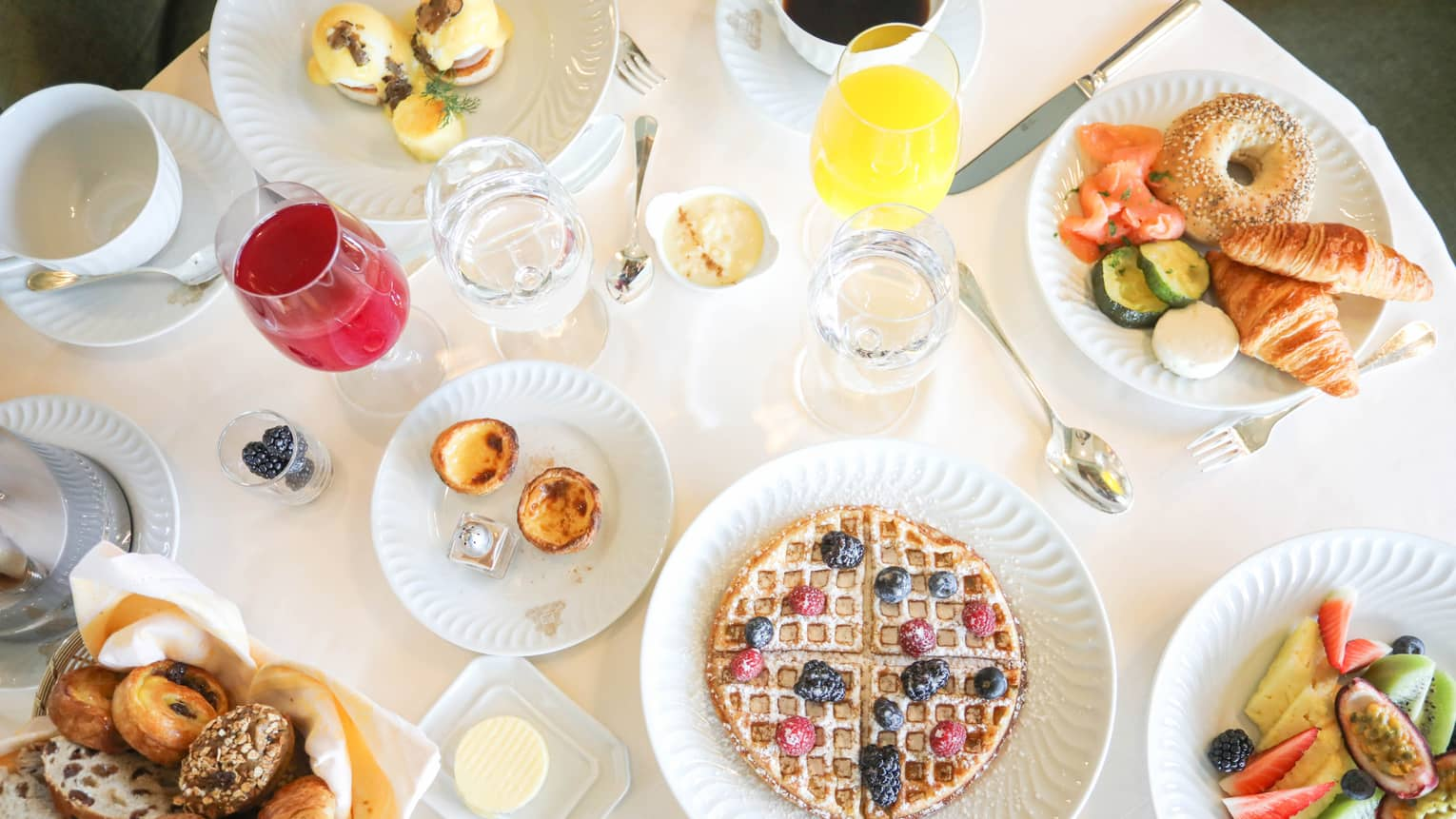 Aerial view of breakfast table with waffles, fresh fruit, pastries and juice in wine glasses