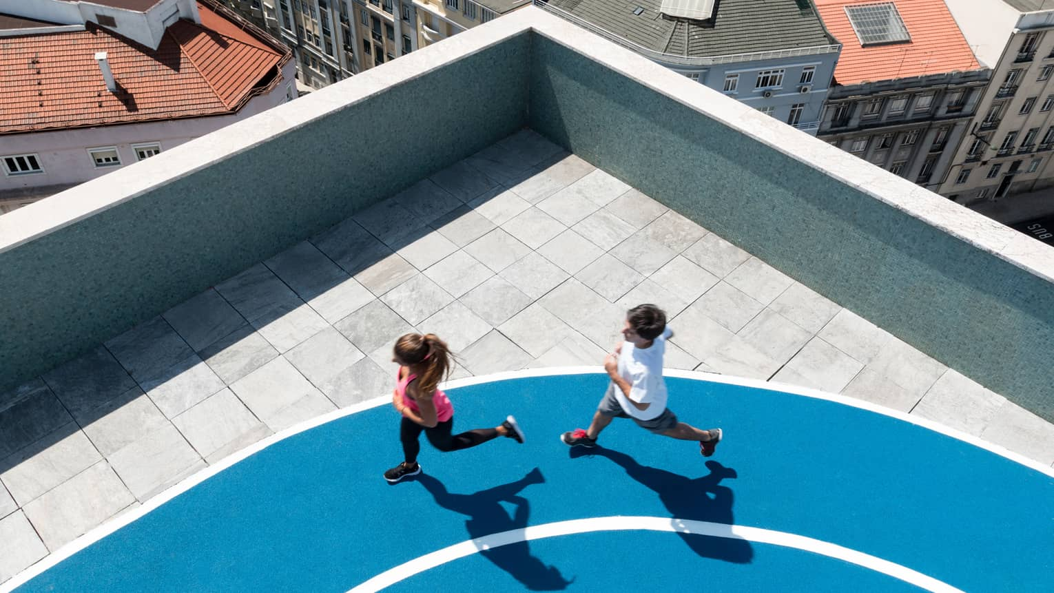 Aerial view of man and woman running on blue jogging track, city rooftops seen below