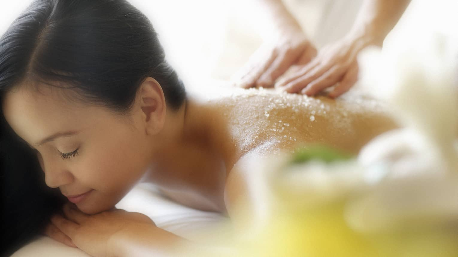 Woman lying down with eyes closed as hands massage salt scrub into shoulders