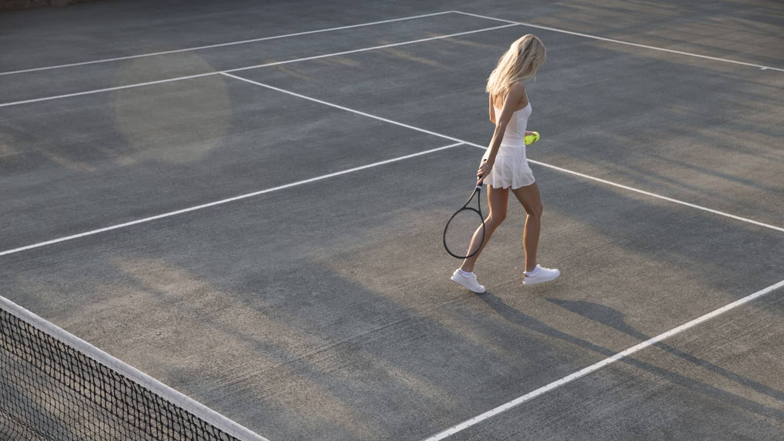 A woman wearing a white tennis dress and shoes walks toward the far end of the tennis court holding her racket and tennis ball