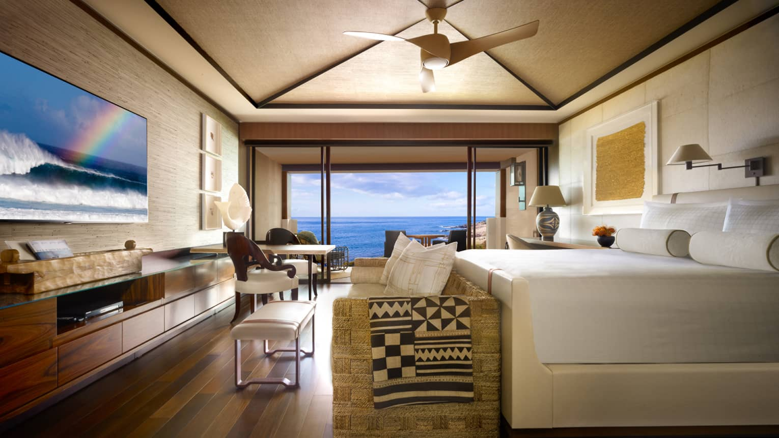 Oceanfront Room bed, small sofa and bench at foot, TV screen displaying ocean waves, rainbow