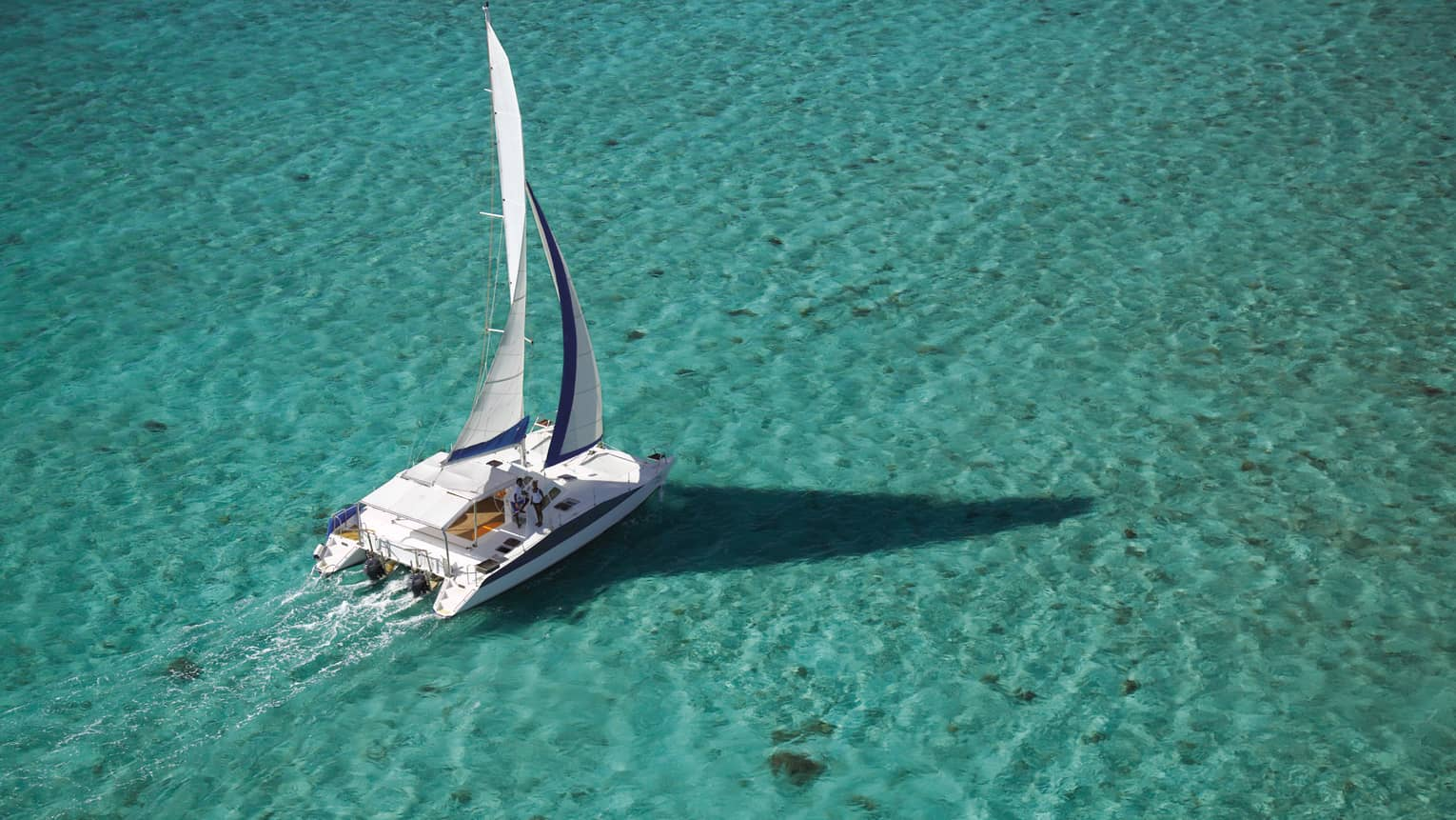 Aerial view of white yacht, sail on turquoise water in lagoon