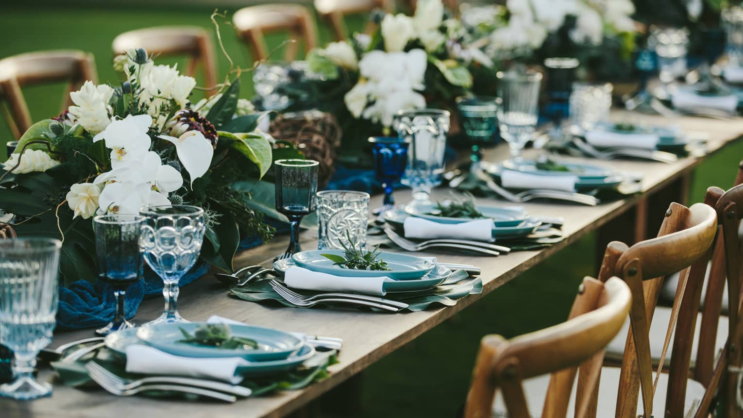 A close up of a long wooden table set with blue plates, eclectic blue and clear glassware, white napkins and green and white floral arrangements all the way down the center of the table