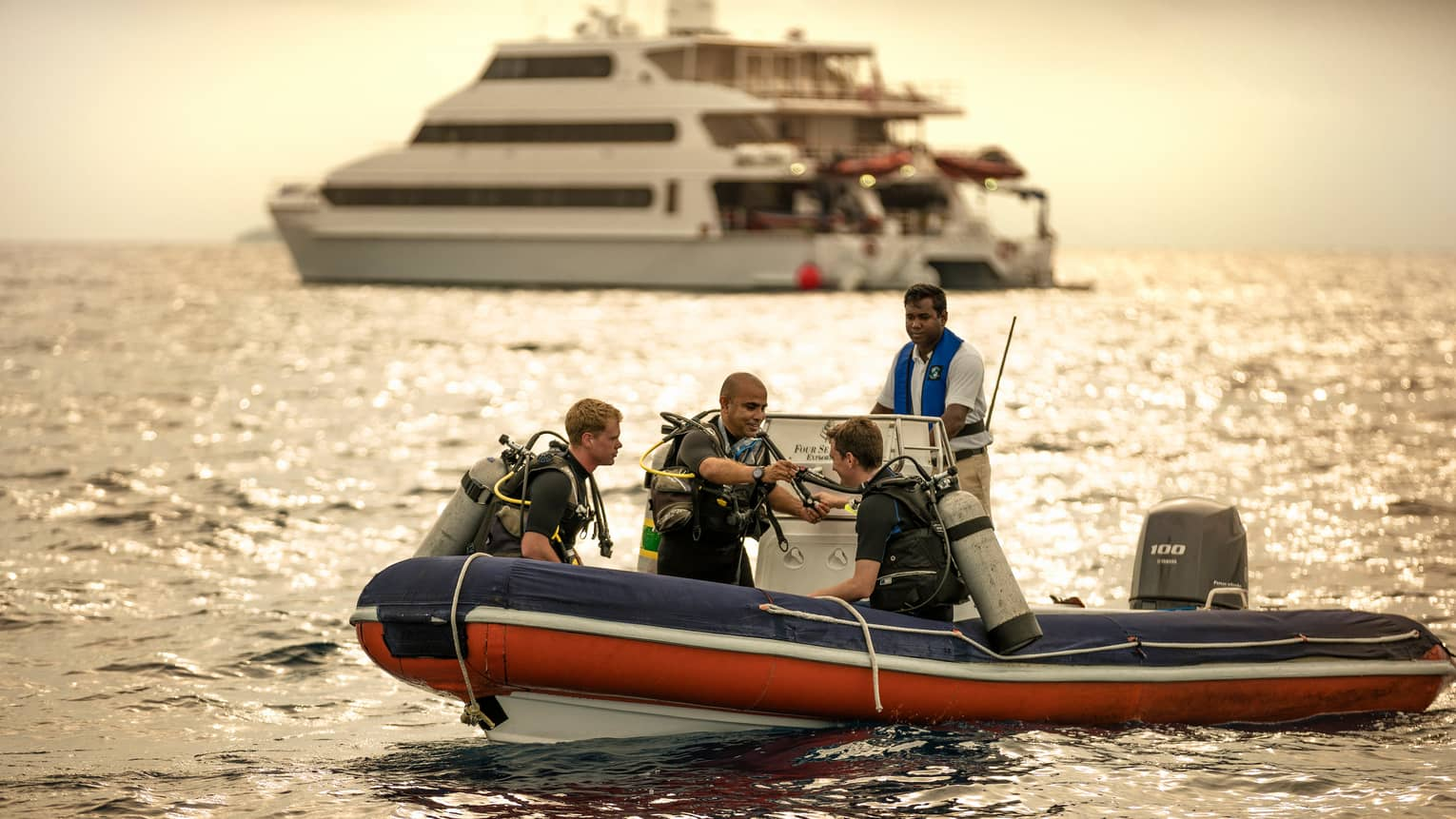 Scuba divers sit on inflatable boat, prepare to dive, yacht in background